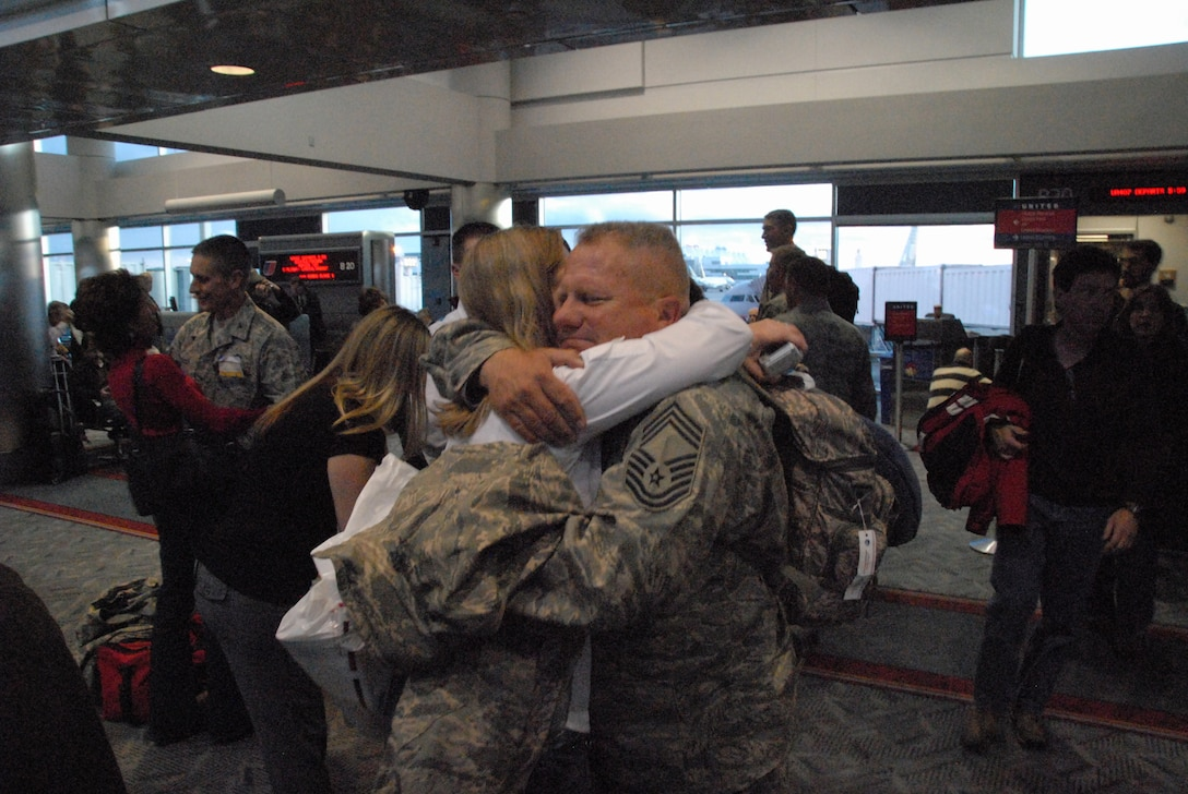 Chief Master Sergeant James Martin hugs his wife, Kellie, after returning from a six-month deployment to Afghanistan.  Chief Martin worked as part of a six-man Facilities Engineer Team responsible for design and construction project management.
