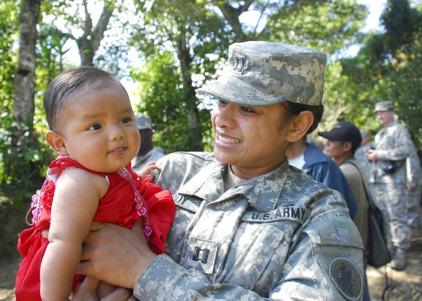 SOTO CANO AIR BASE, Honduras - Army Capt. Liliu Moody, Joint Task Force-Bravo, takes a break from distributing mattresses to spend time with 5-month-old Jalia in El Mangos, Honduras, Jan. 30.  The men and women of JTF-B distributed more than 200 mattresses to people in three Honduran villages including Los Mangos.  (US Air Force photo/Tech Sgt. Rebecca Danét)