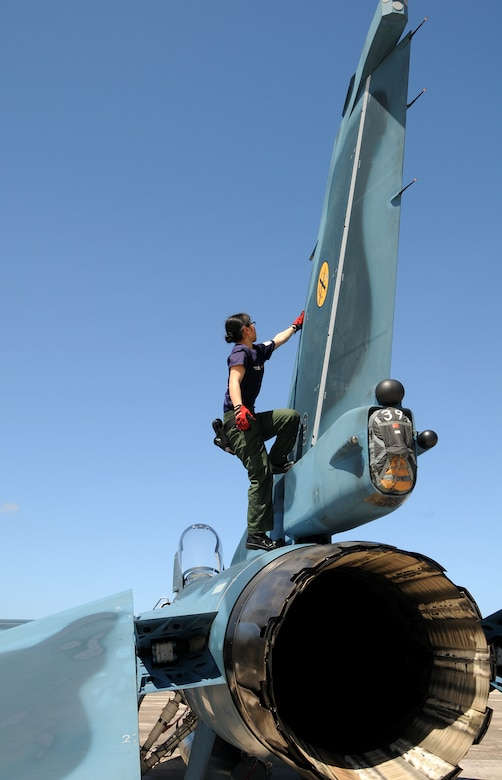 ANDERSEN AIR FORCE BASE, Guam - Japan Air Self Defense Force maintainer Staff Sgt. Teraya Miho inspects the vertical stabilizer of an JASDF F-2 fighter after the aircraft arrived here Jan. 30 for participation in Cope North. This is the tenth time the United States and Japan have held a Cope North exercise on Guam, and it will be the fourth time that the JASDF will use live ordnance. (U.S. Air Force photo by Airman 1st Class Courtney Witt)