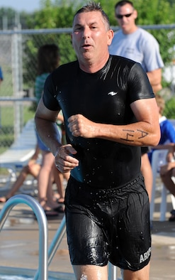 WHITEMAN AIR FORCE BASE, Mo. -  Senior Master Sgt. Mark Mock, 442nd Fighter Wing's Team A, in a fit of urgency, runs out of the pool towards the bike rack to begin the next portion of the triathlon. (U.S. Air Force photo/Senior Airman Cory Todd)