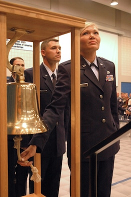 """New 2nd Lt. Teah Johnson rings the commissioning bell during her graduation from the Academy of Military Science at the I.G. Brown Air National Guard Training and Education Center at McGhee Tyson Air National Guard Base, Tenn., on June 26, 2009. She will become a navigator on a C-130 cargo aircraft for the 182nd Airlift Wing of the Illinois Air National Guard. Officer candidates of class """"O-2009-4,"""" who graduated today, are members of the last officer commissioning program class at TEC. (Photo by Master Sgt. Greg Rudl, National Guard Bureau)"""