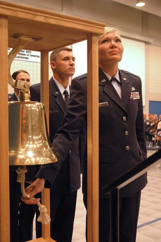 "New 2nd Lt. Teah Johnson rings the commissioning bell during her graduation from the Academy of Military Science at the I.G. Brown Air National Guard Training and Education Center at McGhee Tyson Air National Guard Base, Tenn., on June 26, 2009. She will become a navigator on a C-130 cargo aircraft for the 182nd Airlift Wing of the Illinois Air National Guard. Officer candidates of class ""O-2009-4,"" who graduated today, are members of the last officer commissioning program class at TEC. (Photo by Master Sgt. Greg Rudl, National Guard Bureau)"