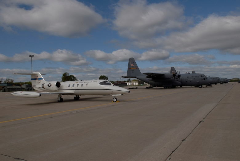 """133rd Airlift Wing  C-130 """"Hercules"""" are lined up next to a 375th Airlift Wing C-21 Learjet from Scott Air Force base. The C-21 is a twin turbofan engine aircraft used for cargo and passenger airlift. Both units are conducting training missions at Volk Field, Wis. on May 16, 2009. Hundreds of men and women from the Minnesota Air National Guard unit joined others from Scott Air Force Base, Illinois for Readiness Safeguard in preparation for an Operational Readiness Inspection. USAF Official photo by Technical Sgt. Erik Gudmundson.(Released)"""