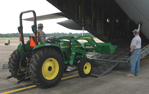 """Chief Master Sgt. Lynn Whited drives a tractor into a 908th Airlift Wing C-130 aircraft Monday that is headed for the Dominican Republic. A member of the 908th's 25th Aerial Port Squadron, Chief Whited loaded the tractor and several other items acquired by Daystar Baptist Missions to be used for humanitarian relief in the Dominican Republic. Lt. Col. Jerry Lobb, 908th public affairs officer, said the cargo was being flown """"space available"""" in accordance with the 1985 Denton Amendment, named after U.S. Sen. Jeremiah A. Denton of Alabama. The Denton Amendment allows nonprofit, charitable organizations access to unused cargo space on Air Force aircraft for humanitarian aid, Colonel Lobb said. He added transportation of the cargo is a """"by-product"""" of mission training. (U.S. Air Force photo/Lt. Col. Jerry Lobb)"""