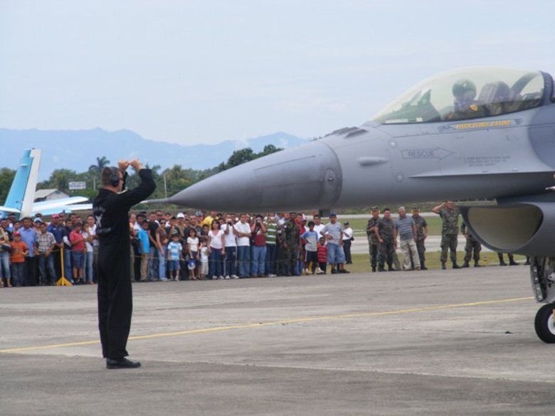 A crowd of air show attendees here cheer as a crew chief from the Viper East F-16 Demo Team marshals an F-16 after an aerial demonstration June 21. More than 30 Airmen participated at the international air show June 20-21. The more than $35,000 proceeds from the show will help build a children?s intensive care unit at a local hospital.