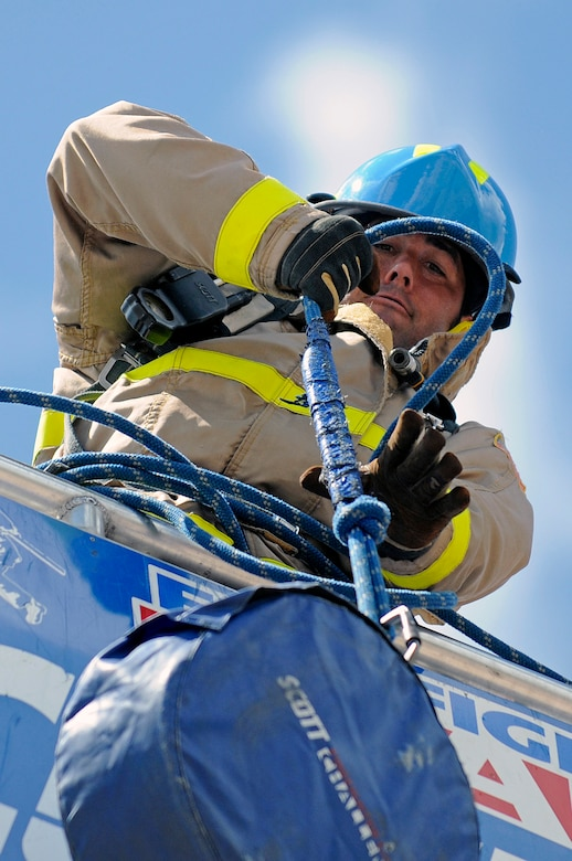 Team USAFA relay member firefighter Steve Hardman hoists a 45-pound hose up a five-story tower during a regional Firefighter Challenge at the U.S. Air Force Academy, Colo., June 27. (U.S. Air Force photo/Mike Kaplan)