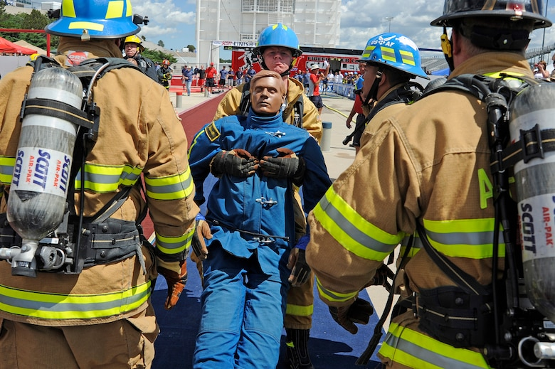 """Airman 1st Class Matthew Murrell drags a 175-pound life-size """"Rescue Randy"""" mannequin during the final leg of a relay during a regional Firefighter Challenge held June 26-27 at the U.S. Air Force Academy in Colorado Springs, Colo. (U.S. Air Force photo/Mike Kaplan)"""