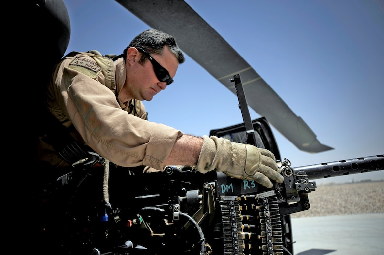 Tech. Sgt. Brock Woodward performs a preflight inspection of a .50 caliber machine gun June 23 at Camp Bastion, Afghanistan. Sergeant Woodward is a flight engineer with the 129th Expeditionary Rescue Squadron. (U.S. Air Force photo/Staff Sgt. Shawn Weismiller)