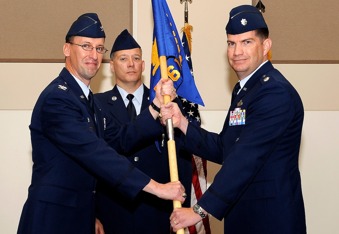BUCKLEY AIR FORCE BASE Colo. – Col. Darren Medlin, 544th Intelligence Group commander, Peterson AFB, passes command of the 566th Intelligence Squadron over to new commander, Lt. Col. David Scanlon here, June 30. (U.S. Air Force photo by: Senior Airman Steven Czyz)