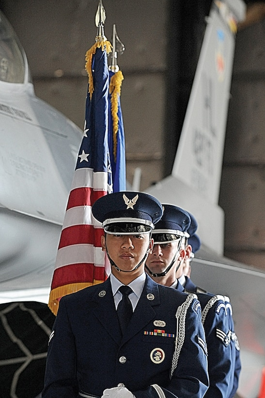 The Hill Air Force Base Honor Guard stand beside the 421st Fighter Squadron F-16 Fighting Falcon in Hangar 37 before a memorial service June 26 for Capt. George Houghton.  Captain Houghton, 421st FS pilot, died during an F-16 accident at the Utah Test and Training Range June 22.