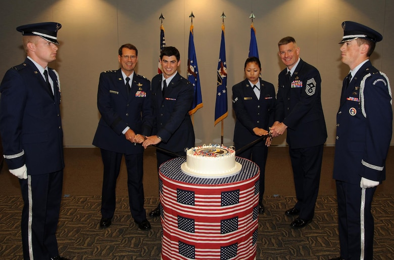 Lt. Gen. Tom Sheridan, Space and Missile System Center commander, presided over the ceremony commemorating SMC's 55th Anniversary, July 1.   LAAFB's youngest officer and airman Lt. Alex Menas and Airman 1st Class Larissa Lilie, assisted by Chief Master Sgt. Stephen Ludwig, SMC command chief, and the general, had the honor of cutting the ceremonial cake. Honor guard members Lt. Josh Duckett and Lt. Kevin Williams also are pictured. (Photo by Lou Hernandez)