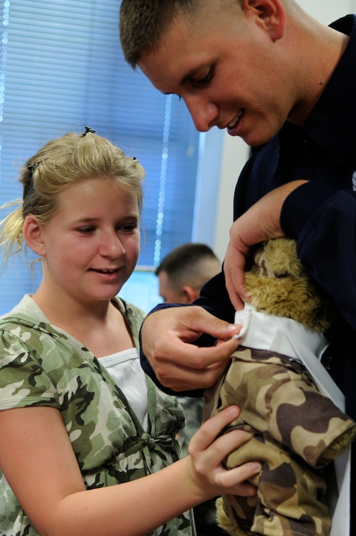 "Bailey Reese, founder and president of the non-profit organization, Hero Hugs, and Staff Sgt. Michael Doss, United States Air Force Honor Guard Drill Team member, attach ""Hero"" with the highest level Drill Team ascot July 7 on Bolling Air Force Base D.C. Hero is the mascot for Hero Hugs and has toured Iraq and Afghanistan as a symbol of Bailey's gratitude for military servicemembers.  (U.S. Air Force photo by Staff Sgt. Dan DeCook)"