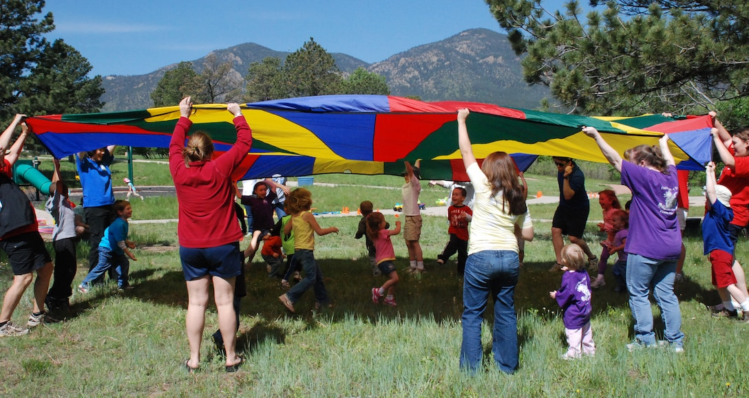 Children play under and around a parachute during Fit for the Future, Meet Me in the Park activities June 3. The program runs from 9 to 11 a.m. Tuesdays in Pine Valley and Thursdays in Douglass Valley through the end of July. (U.S. Air Force photo/Ann Patton)