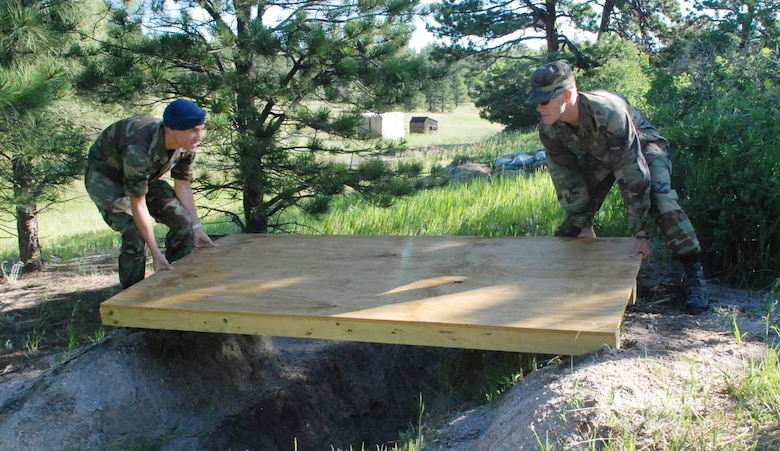 Cadet 2nd Class Christopher Molstad and Cadet 1st Class Justin Fisk ready Operation Warrior foxholes with overhead defenses. The area services ground combat tactics. (U.S. Air Force photo/Ann Patton)