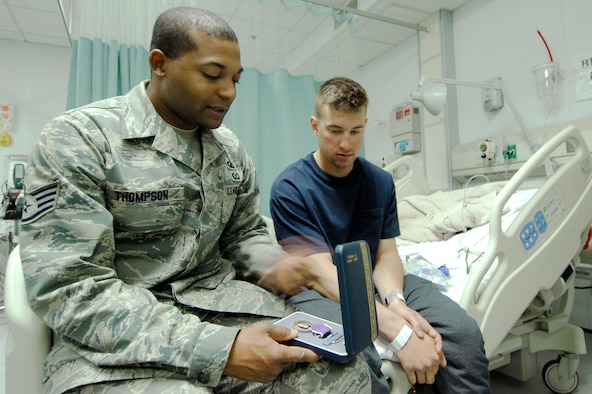 Staff Sgt. Christopher Thompson visits with a patient at the Craig Joint-Theater Hospital at Bagram Air Field, Afghanistan, July 1. Sergeant Thompson, the NCO in charge of hospital chapel operations, is deployed from the U.S. Air Force Academy in Colorado Springs, Colo. (U.S. Air Force photo)