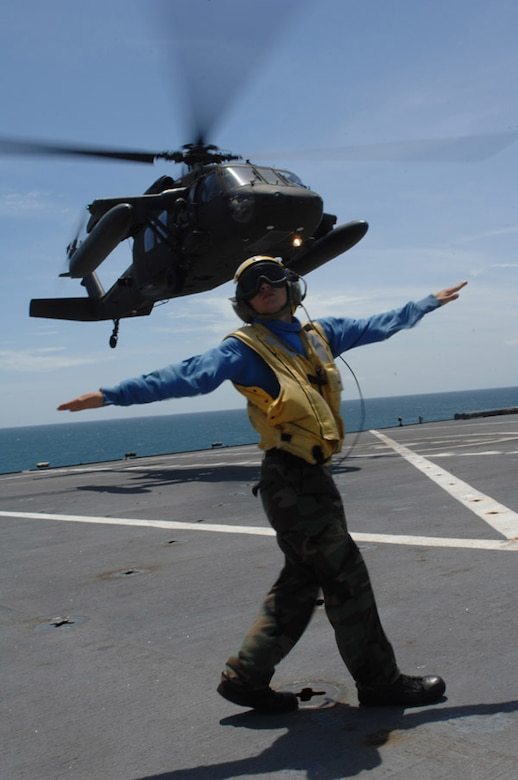 CORINTO, Nicaragua — Aviation Boatswain's Mate 3rd Class Matthew Shaw directs a UH-60 Army Blackhawk helicopter performing Deck Landing Qualifications aboard hospital ship USNS Comfort here July 9 during Continuing Promise 2009 (CP09).  The helicopter is assigned to Joint Task Force Bravo, U.S. Southern Command's forward-deployed response force stationed in Soto Cano AFB, Honduras, and is assisting CP09 teams with personnel movement and logistics here.  CP09 combines U.S. military and interagency personnel, non-governmental organizations, civil service mariners, academic and partner nations to provide medical, dental, veterinary and engineering services afloat and ashore alongside host nation personnel.  (U.S. Air Force photo by Senior Airman Jessica Snow)