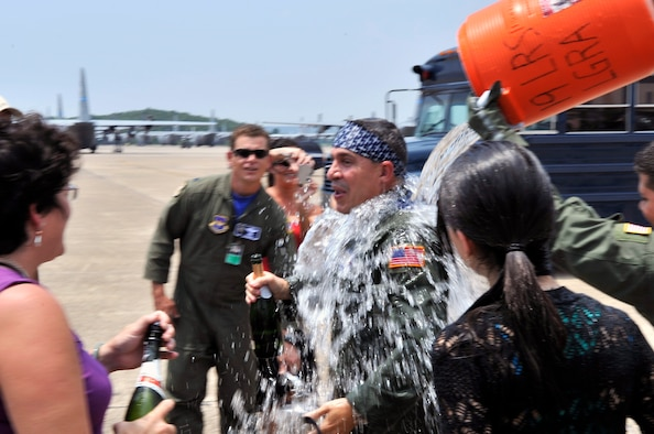 Col. Mark Vlahos, 314th Airlift Wing vice commander, is doused by friends and family members at his final flight at Little Rock Air Force Base July 10. The colonel's next assignment is at Randolph AFB, Texas where he will serve as the 19th Air Force assistant director of operations. The colonel has served as the 314 AW's vice commander since July 2007. The 314 AW's mission is to train C-130 aircrews for all services in the Department of Defense, Coast Guard and 34 allied nations, as well as C-21 aircrew through the 45th Airlift Squadron at Keesler AFB, Miss. (U.S. Air Force photo by Staff Sgt. Chris Willis)