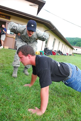 167th Airlift Wing member, Master Sergeant Kelley McKinney, a TAC (Train, Advise, Counsel) leader for the West Virginia Youth Leaders Camp, instructs a camper on proper push-up technique on the first day of the camp at Camp Dawson near Kingwood, WV. Sixty-six high schoolers from West Virginia participated in the week-long camp now in its forty-third year. Youth Leaders Camp, geared toward building confidence and instilling leadership skills, challenges the campers with mentally and physically demanding activities. (U.S. Air Force Photo by MSgt Emily Beightol-Deyerle)