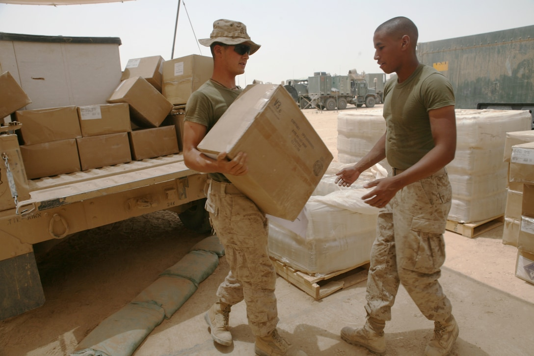 Marines with motor transport section, Headquarters and Service Company, Task Force 3rd Light Armored Reconnaissance Battalion, Regimental Combat Team 8, offload supplies to prepare them for a logistics movement, or logpack, July 11, 2009, at Sahl Sinjar, Iraq.  Logpacks are meant to supply companies operating throughout the battalion area of operations who aren't able to supply themselves due to mission requirements.
