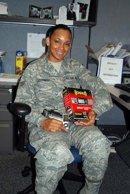 Senior Airman Allancia Sorhaindo, 315th Airlift Wing military pay technician, shows off a few of the benefits of participating in the Get 1 Program. (U.S. Air Force photo/Captain Bryan Lewis)