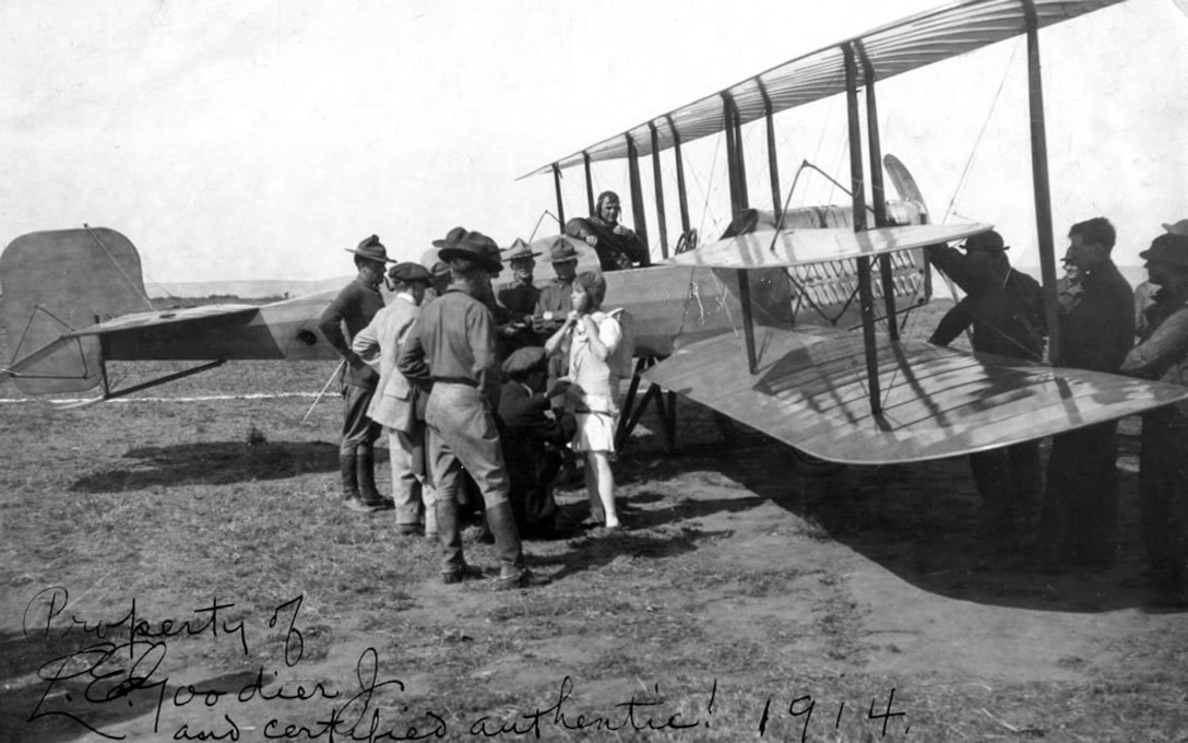 """The figure in white is presumably Miss """"Tiny"""" Broadwick, the first woman to make a parachute jump from an airplane. She jumped at North Island on 12 and 14 September 1914 from an Army Martin plane flown by Oscar Brindley."""