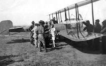 "The figure in white is presumably Miss ""Tiny"" Broadwick, the first woman to make a parachute jump from an airplane. She jumped at North Island on 12 and 14 September 1914 from an Army Martin plane flown by Oscar Brindley."