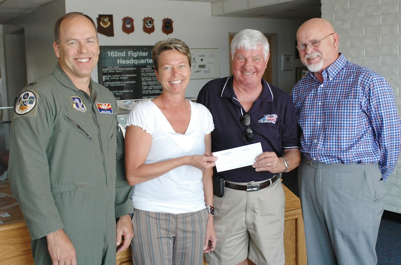 (From the left) Col. Greg Stroud, 162nd Fighter Wing commander, and Barb Gavre, Family Readiness coordinator, accept a check for $606 from Hans Boensel and Michael Leigh of the Green Valley Elks Lodge #2592, July 12. The donation to Family Readiness will help the wing take care of families who need a little extra help and will ensure the wing is able to continue mailing care packages to deployed members. (Air National Guard photo by Capt. Gabe Johnson)