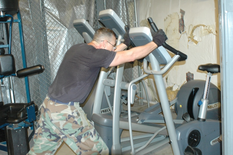 """Tech. Sgt. Mike Tellez, one of several volunteers, moves new cardio equipment into the base gym in building 3, July 14.  Airmen on base are now able to use the  new fitness equipment – previously held in storage on base – due to a """"Commander's Action Line"""" asking Wing Commander Col. Greg Stroud for access to it. (Air National Guard photo by Capt. Gabe Johnson)"""