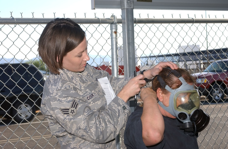 Senior Airman Sarah Cook (left), a civil engineer with the 162nd Fighter Wing, helps Master Sgt. Elizabeth Koller fit her gas mask July 12 as part of a mobility exercise. The wing completed the exercise over the July unit training assembly to enhance readiness among unit members.(Air National Guard photo by Staff Sgt. Sarah Elliott)