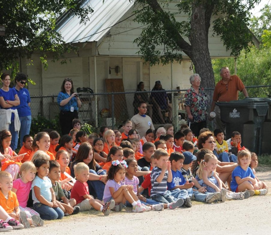 Residents of Eden, Texas watch as a suspected drug house is demolished.