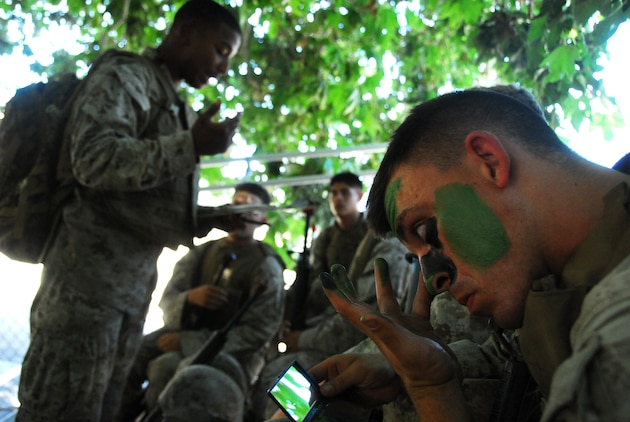 Lance Cpl. Tyler M. Peha, Yuma Headquarters and Headquarters Squadron military policeman, applies camouflage paint as Sgt. Willard Smiley, Search and Rescue quality assurance representative, briefs the squad before a patrol during the Enhanced Combat Skills course July 15, 2009, at Camp Pendleton, Calif. The Marines learned the importance of ensuring that each person involved with a mission is completely informed about every aspect from alternate routes to rally points.