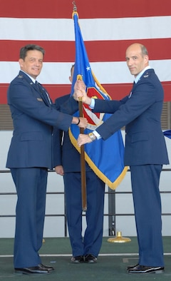 Maj. Gen. Frank Padilla, 10th Air Force commander, left, and Col. Jeffrey Mineo, 940th Wing commander, display the new 940th Wing flag during the 940th re-designation ceremony July 11. The ceremony officially deactivated the 940th Air Refueling Wing and stood up the 940th Wing. (Photo by Tech. Sgt. Luke Johnson)