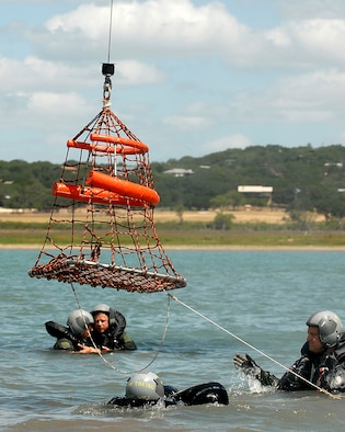 "Lt. Col. Michael ""Bones"" McCoy (right), an F-16 pilot assigned to the 149th Fighter Wing, Texas Air National Guard, Lackland Air Force Base, Texas, guides an aerial rescue basket to other members.  Col. McCoy underwent water survival training as part of an annual training requirement at Canyon Lake, Texas, July 11, 2009.  (U.S. Air Force photo/Master Sgt. Robert Shelley)"