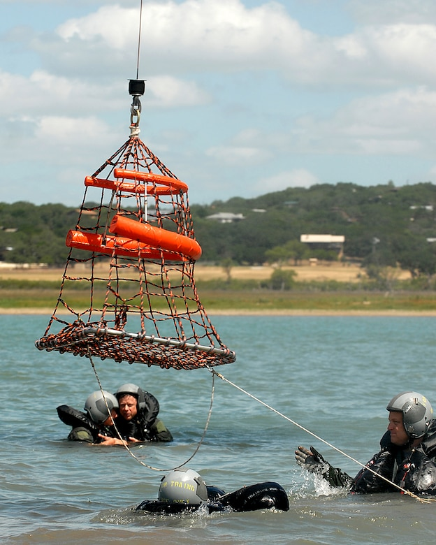 """Lt. Col. Michael """"Bones"""" McCoy (right), an F-16 pilot assigned to the 149th Fighter Wing, Texas Air National Guard, Lackland Air Force Base, Texas, guides an aerial rescue basket to other members.  Col. McCoy underwent water survival training as part of an annual training requirement at Canyon Lake, Texas, July 11, 2009.  (U.S. Air Force photo/Master Sgt. Robert Shelley)"""