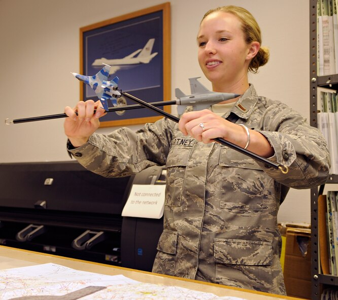 SPANGDAHLEM AIR BASE, Germany – 2nd Lt. Maureen Hartney, 52nd Operations Support Squadron officer in charge of intelligence standards and evaluations, demonstrates air-to-air tactics using aircraft models in the intelligence flight of Spangdahlem Air Base's 52nd OSS July 14. Intel Airmen conduct training on air-to-air, surface-to–air and ground threats. (U.S. Air Force photo by Senior Airman Benjamin Wilson)