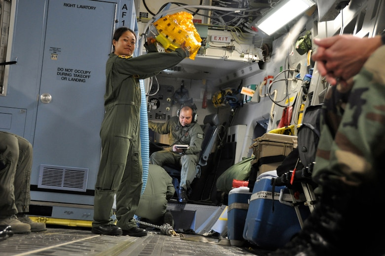 Tech. Sgt. Kimberly Kido demonstrates the proper use of the Emergency Passenger Oxygen System to passengers before departing Hickam Air Force Base, Hawaii, for Kupang, Indonesia, July 14 to support of Operation Pacific Angel 2009. Sergeant Kido is a loadmaster with the Hawaii Air National Guard?s 204th Airlift Squadron at Hickam. Pacific Angel is a Pacific Air Forces humanitarian assistance operation in the Asia-Pacific region led by 13th Air Force at Hickam AFB. (U.S. Air Force photo/Tech. Sgt. Cohen A. Young)