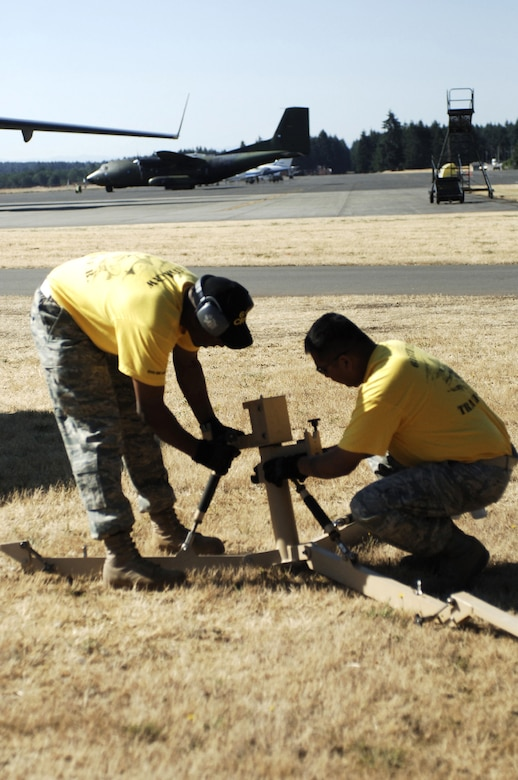 Airmen from the 615th Contingency Response Wing at Travis Air Force Base, Calif., work together to set up a satallite for the SPICE competition at the Air Mobility RODEO 2009 at McChord AFB, Wash. (U.S. Air Force Photo/2nd Lt. Erika Wonn)