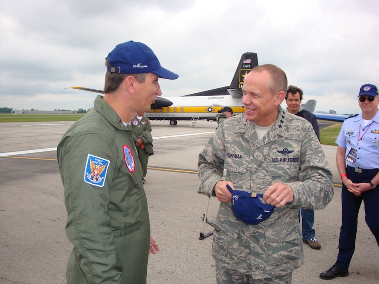 """DAYTON, Ohio (AFMCNS) – Gen Donald Hoffman, commander of Air Force Materiel Command, converses with Lt Col José Aguinaldo de Moura , commander of Brazil's Esquadrilha da Fumaça, or """"Smoke Squadron."""" The Brazilian Smoke Squadron performed July 18 and 19 at the 2009 Vectren Dayton Air Show at the Dayton International Airport. General Hoffman met with Colonel Moura's team, which is known for its fast-paced, close-up aerobatics and smoke displays, after its Saturday performance. Also on hand was Maj Gen Stefan Egon Gracza, Brazilian Defense and Air Attaché (background, right). The team flies the Embraer T-27 Tucano aircraft. (Air Force photo by Kathleen A.K. López)"""
