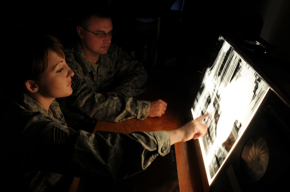 Staff Sgt. Cortney Coker, 48th Equipment Maintenance Squadron Non-Destruction Inspection journeyman, looks over an x-ray image of a section of F-15E Strike Eagle with Tech. Sgt. Sterling Rosenau, an F-15 phase crew chief with the same squadron. X-rays of the aircraft are taken pre and post inspection and then compared for variations or defects. (U.S. Air Force photo by Staff Sgt. Nathan Gallahan)