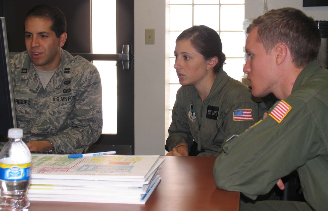 (Left to right) Capt. James Rodriguez from the Air Force Operational Test and Evaluation Center's Detachment 3 at Kirtland Air Force Base, N.M., works with Cadets First Class Brittney Garrett and Mark Price as they analyze questionnaire and reliability data for the Department of Defense National Airspace System during the U.S. Air Force Academy's Cadet Summer Research Program. During the five-week program, cadets gained hands-on exposure to operational testing processes, products, and experiences. (U.S. Air Force photo).
