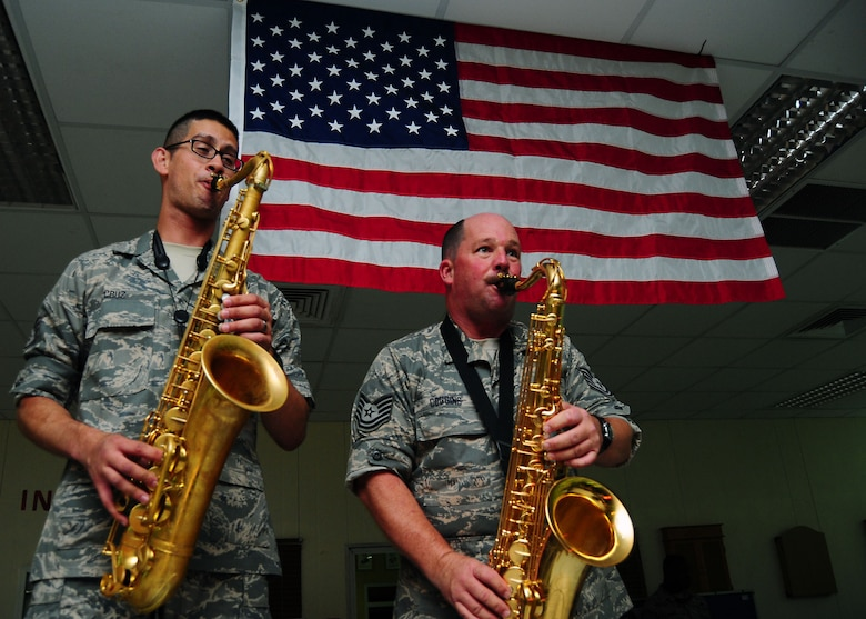 SOUTHWEST ASIA -- Staff Sgt. Jorge Cruz, left, and Brian Coggins, from the Air Force Central Command Sonora band, play saxaphone under the stars and stripes at a performance for the 386th Air Expeditionary Wing July 21. Sergeants Cruz and Coggins are members of the 129th Rescue Wing, Moffet Federal Air Field, Calif. (U.S. Air Force photo/Tony Tolley)