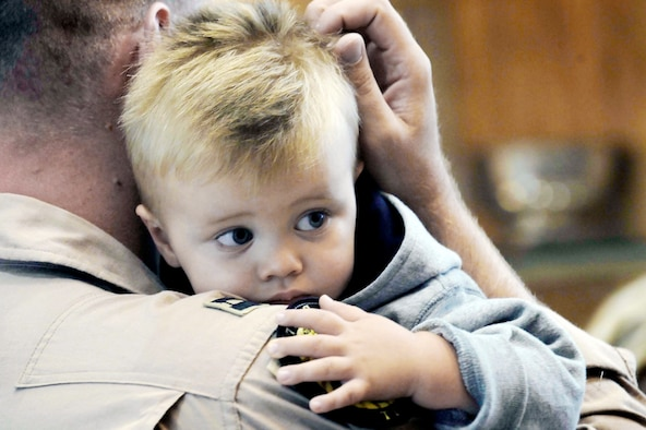 A weapons systems officer assigned to the 37th Bomb Squadron holds his son before deploying July 21 from Ellsworth Air Force Base, S.D. Airmen representing various specialties deployed in support of operations at the 379th Air Expeditionary Wing in Southwest Asia. (U.S. Air Force photo/Airman 1st Class Corey Hook)