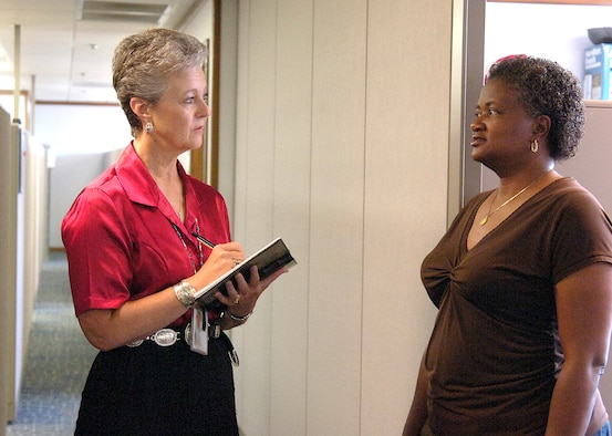 As a unit public affairs representative, or UPAR, workers like Gail Kulhavy, left, share news from their organizations with Tinker and the Air Force.  Ms. Kulhavy visits with co-worker Tanya Whitfield, both from Information Technology in the Oklahoma City Air Logistics Center. (Air Force photo by Margo Wright)