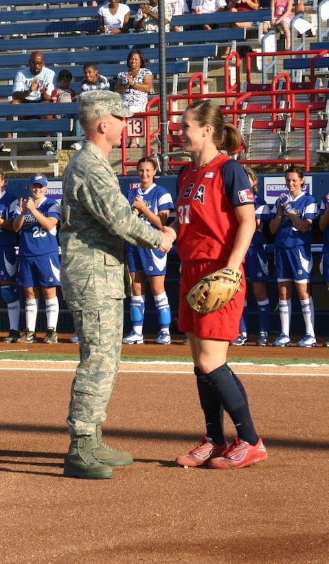 Col. Scott Forest, vice commander, 552 ACW, shakes the Team USA catcher's hand after throwing her the first pitch as part of Military Appreciation Night at the World Cup of Softball July 17.