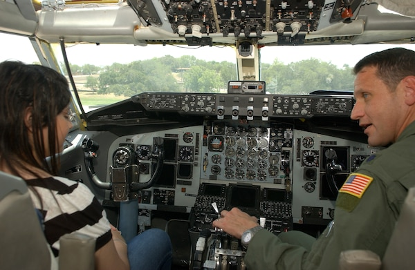 7/18/2009 - Reveca Cahue (left) sits in the cockpit of a KC-135 while Lt. Col. Marc Caudill talks about what it takes to fly the airplane. During her visit to the base July 18, Ms. Cahue also had the opportunity to tour an MH-53 Pave Low helicopter and a C-130 Hercules. (U.S. Air Force photo/Alan Boedeker)