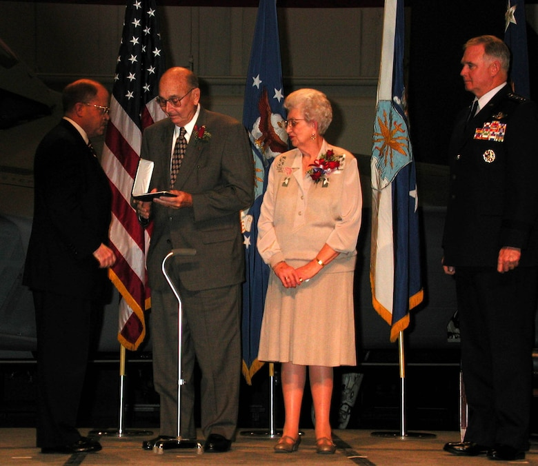 "Sometimes, awards and decorations are presented posthumously. In a ceremony held at the National Museum of the U.S. Air Force on Dec. 8, 2000, Secretary of the Air Force F. Whitten ""Whit"" Peters presented the Medal of Honor to the parents, William F. and Alice Pitsenbarger, of Airman 1st Class William F. Pitsenbarger. Air Force Chief of Staff Gen. Michael E. Ryan (right) and about 1,800 guests attended the ceremony. (U.S. Air Force photo)"