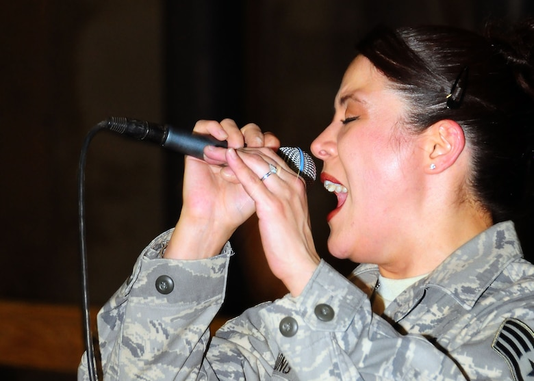 CAMP BUCCA, Iraq-- Staff Sgt. Angie Long, Air Force Central Command Sonora band, sings during a performance for members of Camp Bucca, Iraq on July 22.  Sonora offers a diverse performance repertoire featuring acoustic, electric and bass guitars, keyboards, drums, saxophone and trumpet.  Vocalists round-out the mix and an expert engineer brings it all together.  Sergeant Long is deployed from the 131st Fighter Wing, Air National Guard, Mo., and hails from Nashville, Tenn.  (U.S. Air Force photo/Tech Sgt. Tony Tolley)