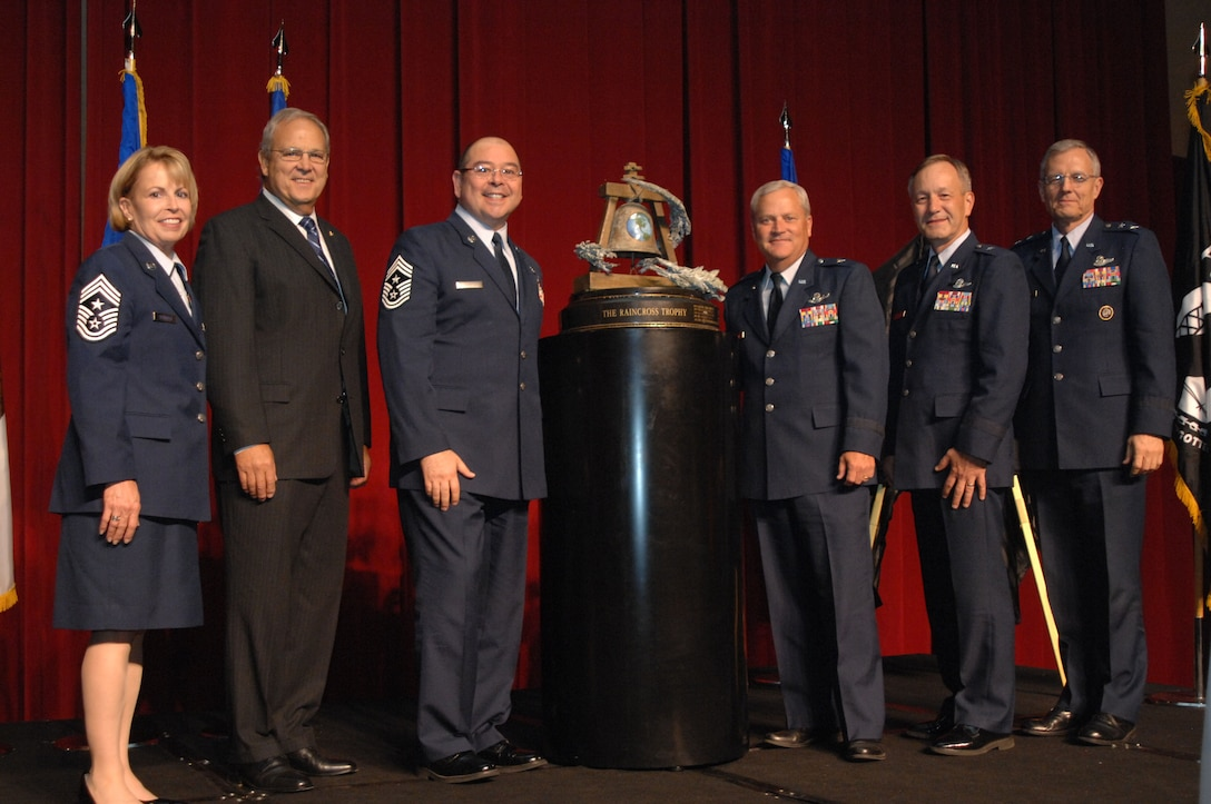 From left to right, Chief Master Sgt. Patricia Thornton, Fourth Air Force Command Chief; Mr. Roger Rupp, Greater Riverside Chambers of Commerce Military Affairs Committee Chairman; Brig. Gen. James Melin, 452nd Air Mobility Wing Commander; Chief Master Sgt. Agustin Huerta, 452nd AMW Command Chief;  Brig. Gen. Eric W. Crabtree, Headquarters Fourth Air Force  Commander; and Maj. Gen. John M. Howlett, Deputy Director, U.S. Strategic Command, pose with the Raincross Trophy after it was awarded to the 452nd AMW during the 11th Annual Raincross Trophy Dinner held July 23, 2009, at the Riverside Convention Center, Riverside, Calif.. The dinner is hosted by the Greater Riverside Chambers of Commerce Military Affairs Committee to honor and recognize the 11 wings and two groups in 4th Air Force.  (U.S. Air Force photo/ Senior Master Sergeant Kim Allain)  (released)