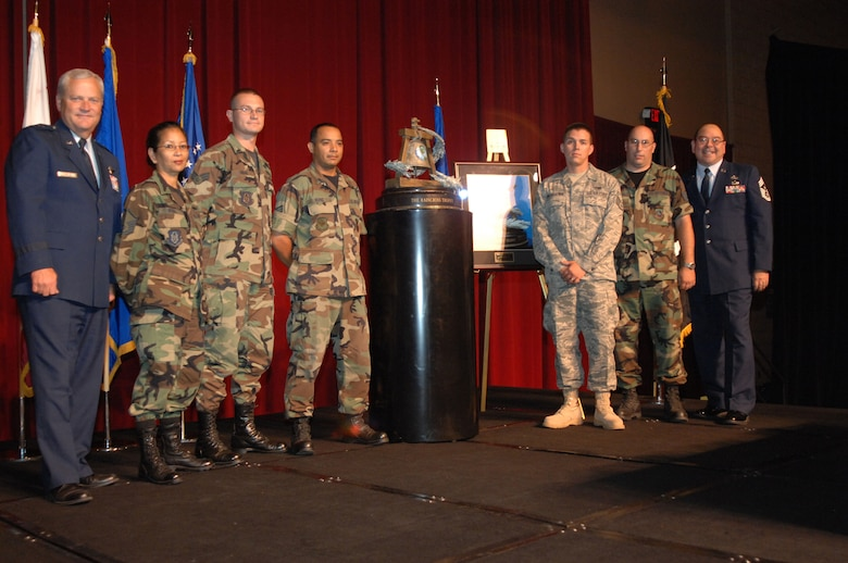 Brig. Gen. James Melin, left, Commander, 452nd Air Mobility Wing, March Air Reserve Base, Calif., and Chief Master Sgt. Agustin Huerta, 452nd AMW Command Chief, far right, pose with members of the 452nd Logistics Readiness Squadron with the Raincross Trophy after it was awarded to the 452nd AMW at the 11th Annual Raincross Trophy Dinner held July 23, 2009, at the Riverside Convention Center, Riverside, Calif. The dinner is hosted by the Greater Riverside Chambers of Commerce Military Affairs Committee to honor and recognize the 11 wings and two groups in 4th Air Force.  (U.S. Air Force photo/Senior Master Sgt. Kim Allain)  (released)