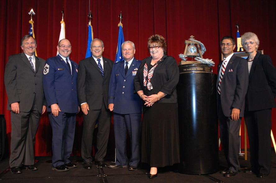 From left to right, Mr. Mike Vanderpool; Chief Master Sgt. Agustin Huerta, 452nd Air Mobility Wing, March Air Reserve Base, Calif., Command Chief; Mr. Roger Rupp; Brig. Gen. James Melin, Commander, 452nd AMW; Ms. Laura Froehlich; Mr. Jamil Dada; and Co. (ret) Nancy Driscoll, pose with the Raincross Trophy after it was awarded to the 452nd AMW at the 11th Annual Raincross Trophy Dinner held July 23, 2009, at the Riverside Convention Center, Riverside, Calif. The dinner is hosted by the Greater Riverside Chambers of Commerce Military Affairs Committee to honor and recognize the 11 wings and two groups in 4th Air Force.  (U.S. Air Force photo/Senior Master Sgt. Kim Allain)  (released)